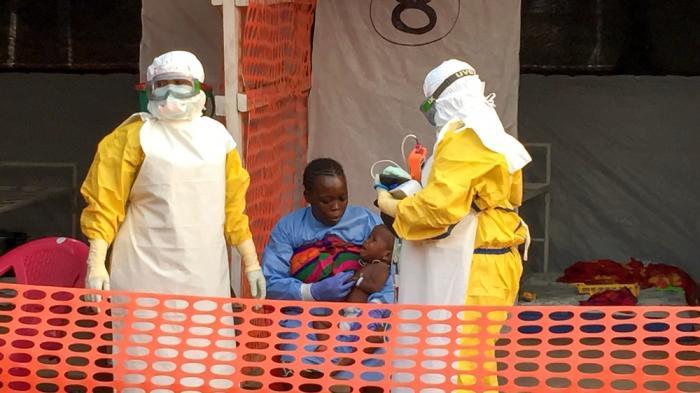 To hjelpearbeidere i beskyttelsesdrakt med mor og barn på et ebolasenter