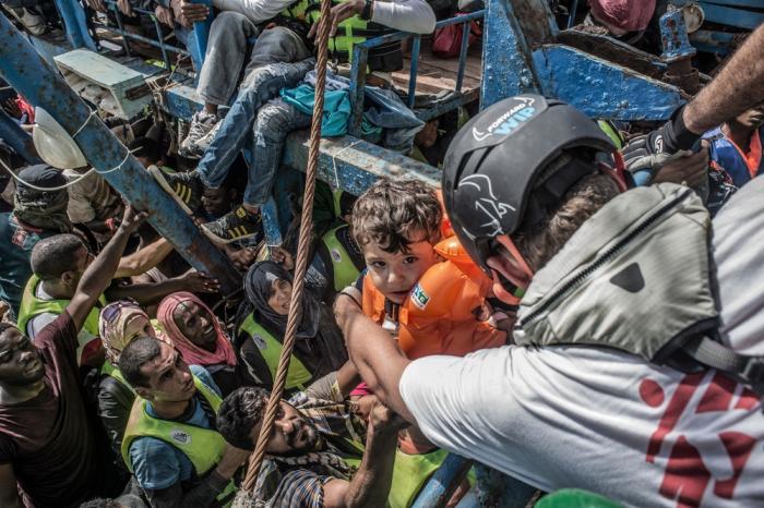 En feltarbeider fra Leger Uten Grenser tar imot et barn som blir løftet ut av en båt full av mennesker.