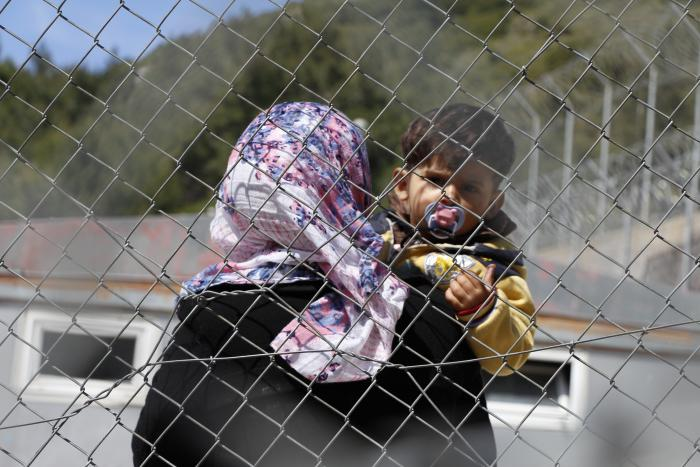 FENSGLET I HELLAS: Umm Akeel (25) og hennes snart to år gamle sønn er to av mange tusen syriske flyktninger og begynner å miste håpet om en trygg hverdag. Den unge moren forteller at hun føler seg som en kriminell i den lukkede leiren på Samos. Foto: Mohammed Ghannam