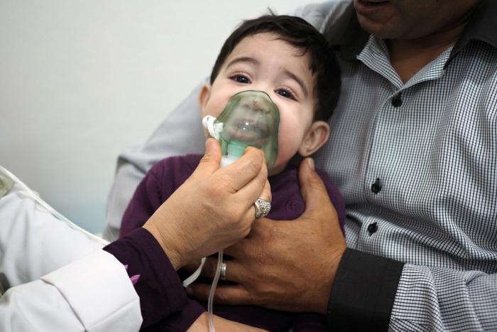 En helsearbeider holder en pustemaske til ansiktet på en liten gutt.