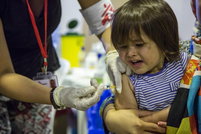 En hjelpearbeider fra Leger Uten Grenser vaksinerer en ung jente.