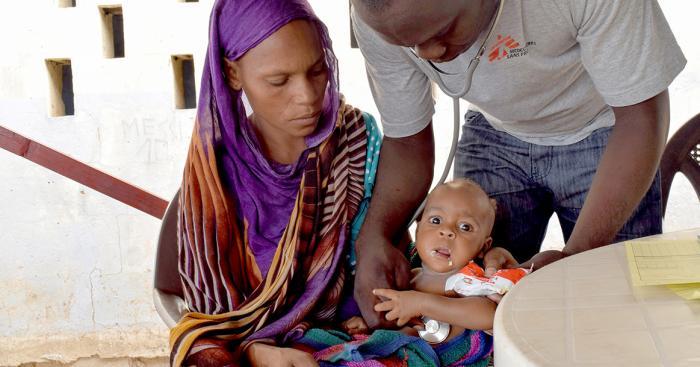 FÅR BEHANDLING: Ziham (6 mnd) sitter på mamma Amaboua Abde (22) sitt fang. I to uker har han blitt behandlet for underernæring på Leger Uten Grensers senter i Tsjad. Her spiser han spesialmaten Plumpy'Nut. Én uke med slik behandling koster 63 kroner. Foto: Charlotte Morris/Leger Uten Grenser