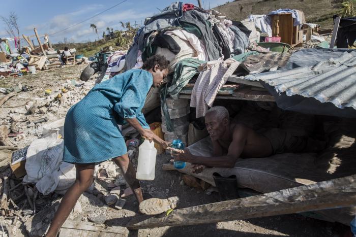 En kvinne gir vann til sin mann, som er for syk til å gå.