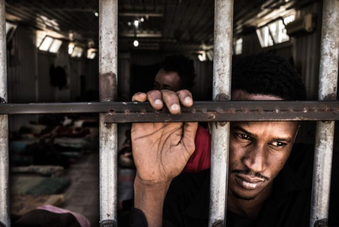 FENGSLET: En eritreer kikker ut av fengselsvinduet i flyktningleiren i Gharyan i Libya. Dette er et av flere hindre mennesker fra det lukkede diktaturet møter før de får sjansen til å søke beskyttelsen mange av dem har krav på i Europa. Foto: Daniel Etter/Redux